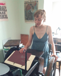 "a lightskinned woman with messy blond hair in a blue sundress stands at a big old letterpress, with one hand on the cover of a purple page reading ""The Forgiveness Poems"""