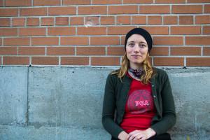 Lisa Baird sits against the bricks
