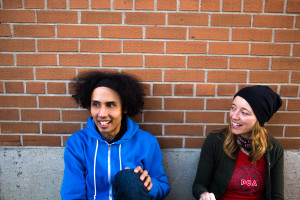 David and Lisa sit laughing against a brickwall